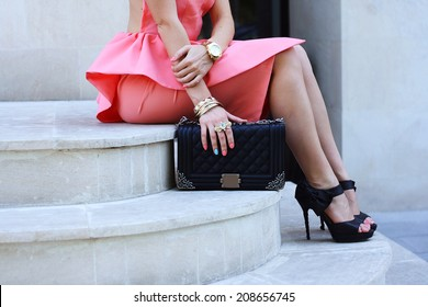 beautiful fashionable woman legs in shoes high heels and handbag at the street