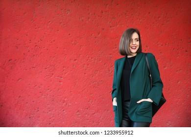 Beautiful fashionable woman near red wall