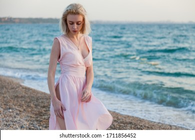 Beautiful fashionable woman in pink dress on the beach by the sea