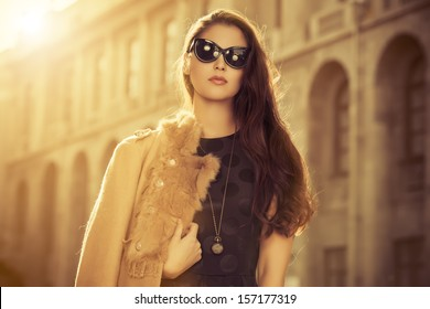 Beautiful fashionable woman standing on the city street. Sepia.