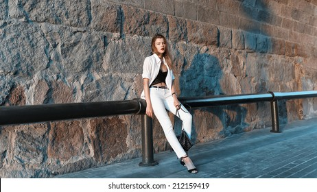 Beautiful fashionable woman standing in white shirt and pants near the wall