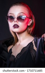 Beautiful fashionable woman in sunglasses on multicolor highlights background