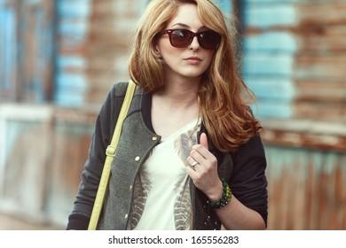 Beautiful fashionable woman in sunglasses walking in the street