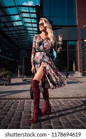 Beautiful fashionable woman walking in the street, wearing sunglasses, nice dress, high heels boots, handbag. Fashion urban autumn photo.