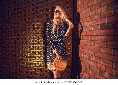 Beautiful fashionable woman walking in the street, wearing sunglasses, nice dots dress, high heels boots, handbag. Fashion urban spring autumn photo.