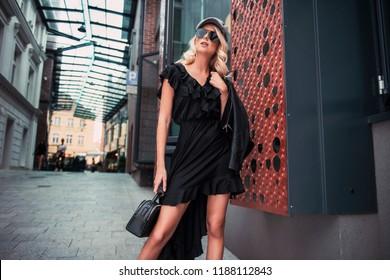 Beautiful fashionable woman walking in the street, wearing sunglasses, nice black dress, high heels boots, flatcap handbag. Fashion urban autumn photo.