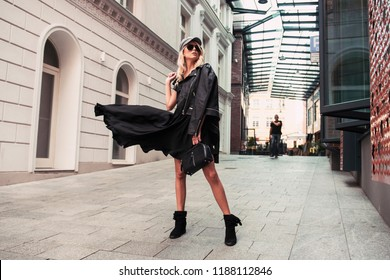 Beautiful fashionable woman walking in the street, wearing sunglasses, nice black dress, high heels boots, flatcap handbag. Fashion urban autumn photo.