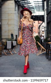 Beautiful fashionable woman walking in the street, wearing sunglasses, nice dress, hat, highheel red boots and a handbag. Fashion urban autumn photo.