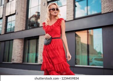 Beautiful fashionable woman walking in the street, wearing sunglasses, nice red dress, high heels boots, handbag. Fashion urban autumn photo.