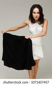 Beautiful fashionable woman in a white dress. Fun like toreador