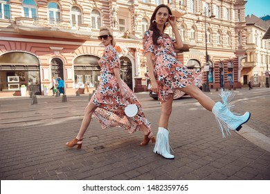 Beautiful fashionable women walking in the street, wearing nice dress, high heels. Fashion urban spring summer photo.