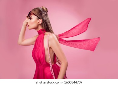 Beautiful fashionable young blonde woman in a studio. Wearing pink elegant flowy dress, high heels. Valentines fashion photo, portrait