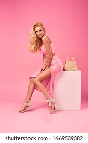 Beautiful fashionable young blonde woman in a studio. Wearing pink white dots elegant dress set, high heels, wicker bag. Spring, summer fashion photo, portrait.