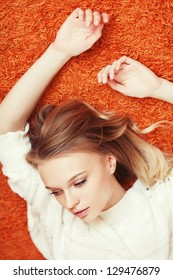Beautiful fashionable young woman lying down, arms up