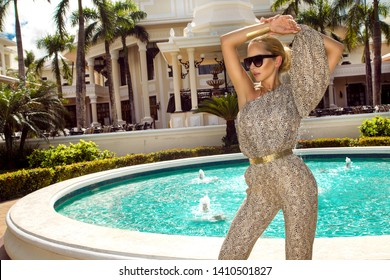 Beautiful fashionable young woman posing in the park, sunglasses, jumpsuit, high heels, blonde hair. Fashion summer photo. Bright colors. Nice view - Image