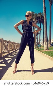 Beautiful fashionable young woman posing in the park, sunglasses, black jumpsuit, high heels, short blonde hair. Fashion summer photo. Bright colors. Nice view