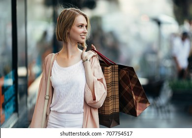 Beautiful and fashionable young woman with shopping bags standing on city street and looking over shoulder