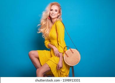 Beautiful fashionable young woman in a studio. Wearing yellow long dress, handbag ,spring summer fashion photo, portrait