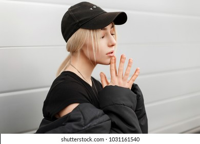 Beautiful fashionable young woman in a stylish black cap in a winter jacket near a modern wall