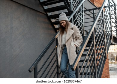 Beautiful fashionable young woman in a stylish knitted hat in a trendy coat looks down and coming down the vintage gray metal staircase in the city. Modern girl model in youth clothes on the stairs.