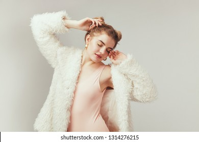 Beautiful fashionble woman in cozy fur coat against light background