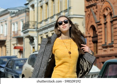 Beautiful fashionista walks along the sidewalk. The weather is hot and she takes off her coat on the go. She is dressed in a yellow sweater and sunglasses.