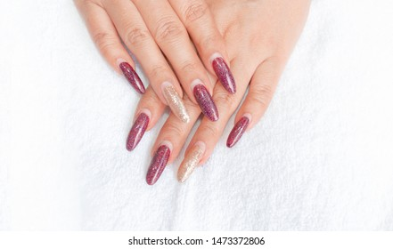 beautiful fashionista woman acrylic extension fingernail stiletto style painting dark red glitter gel nail art and sparkling gold shellac on ring finger,trendy hand manicure after apply one month,