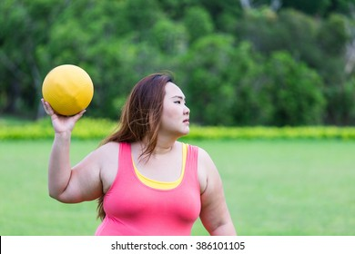 Beautiful fat woman playing dodgeball in the park.