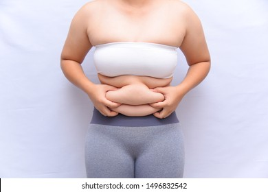A beautiful fat woman wore a white shirt, gray pants and used his hands to hold the excess wax on his stomach. Stand in front of a white background