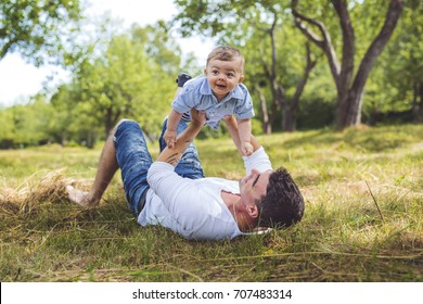 beautiful father little toddler son on the meadow.