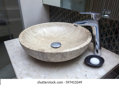 Beautiful faucet and marble sink with soap in a bathroom.
