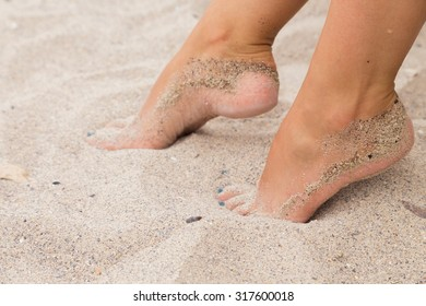 Beautiful feet in the sand. Sea, sand, rest, macro.