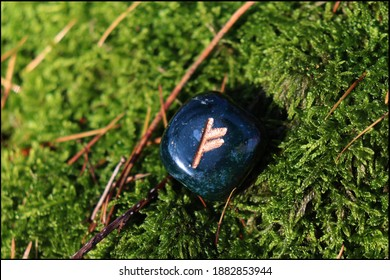Beautiful Fehu Rune made of Bloodstone with mossy background