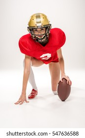 Beautiful female american football player in helmet posing with ball isolated on grey