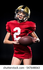 Beautiful female american football player in sportswear and helmet posing with ball isolated on black
