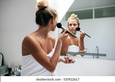 Beautiful female applying cosmetics on her face in bathroom. Female looking into the bathroom mirror and putting on makeup.