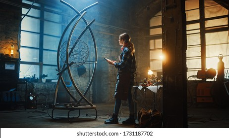 Beautiful Female Artist Comparing a Brutal Metal Sculpture to a Tablet Sketch in Studio. Tomboy Girl Wears Checkered Shirt and Apron. Contemporary Fabricator Creating Abstract Steel Art.