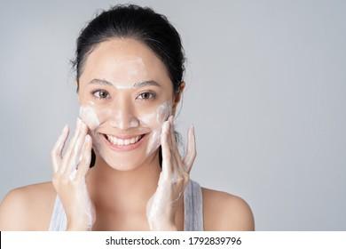 Schöne weibliche asiatische Washface im Studio