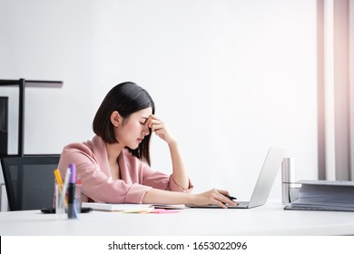 beautiful female asian worker using laptop computer typing on keyboard looking stressed out and annoyed from working in an office with folder files, notebooks, sticky notes for ideas and information
