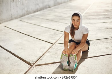 Beautiful female athlete stretching before workout outdoors. Urban sport concept.