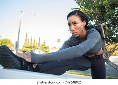 Beautiful female athlete stretching her leg. Focus and determination on her face.