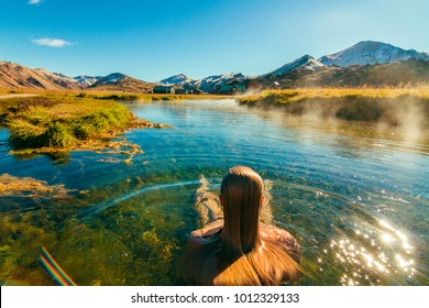 Beautiful female back packer traveler relaxing in the natural hot springs of LANDMANNALAUGAR, Iceland