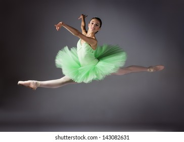 Beautiful female ballet dancer on a grey background. Ballerina is wearing a green tutu and pointe shoes.
