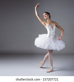 Beautiful female ballet dancer on a grey background. Ballerina is wearing a white tutu and pointe shoes.