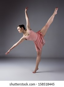 Beautiful female ballet dancer on a grey background. Ballerina is barefoot and wearing an orange dress and leotard.
