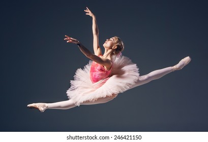 Beautiful female ballet dancer on a grey background. Ballerina is wearing  pink tutu and pointe shoes