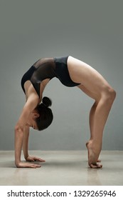 Beautiful female ballet dancer in pose bending backwards on stage, concept power balance coordination flexibility, indoors fitness studio. Artistic performance, acrobat body shape, lifestyle.