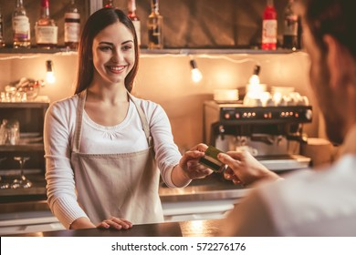 Beautiful female barista is taking a credit card and smiling while working at the bar counter in cafe