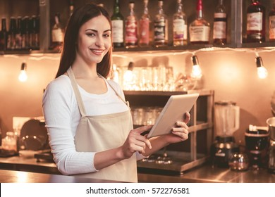 Beautiful female barista is using a digital tablet and smiling while standing at the bar counter in cafe