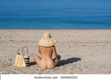 Beautiful female in the bikini and straw hat on the beach and sea background